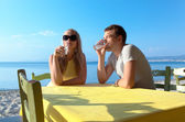 Young couple enjoying drinks at the seaside — Stok fotoğraf