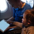 Mother traveling on a plane with her small son — Stock Photo