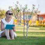 Beautiful woman sitting barefoot on a lawn — Stock Photo #43425403