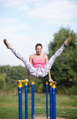 Athletic gymnast exercising on parallel bars — Stock Photo