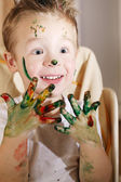 Cute excited boy with hands full of finger paint — Stock Photo