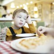 Bored little boy in a restaurant — Stock Photo