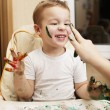 Постер, плакат: Happy little boy doing finger painting