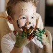 Excited little boy playing with finger paints — Stock Photo