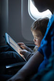 Little boy playing with a tablet in an airplane — Stock Photo