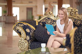 Beautiful woman using tablet in a hotel lobby — Stock Photo