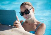 Ung kvinna med en tablett vid poolen — Stockfoto