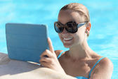 Young woman in a pool using tablet computer — Stock Photo