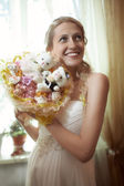 Beautiful young bride with a wedding bouquet — Stock Photo