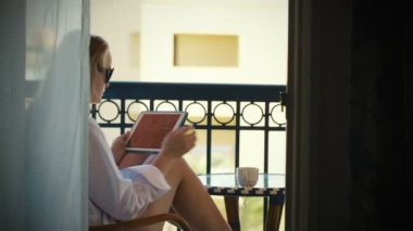 Young woman with touchpad on hotel balcony — Stock Video