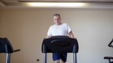 мужчина средних лет, работает на беговой дорожке — Стоковое видео
