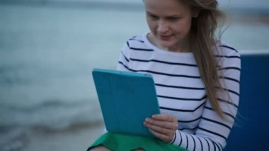 Young woman using tablet PC by the sea — Stock Video