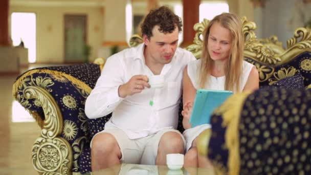 Couple with touchpad on the sofa in the hotel — Vidéo