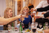 Friends raising their glasses in a toast — Stock Photo