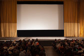 Audience in an auditorium in front of white cinema screen — Stock Photo