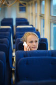 Woman sitting in a train talking on her mobile — Stock Photo