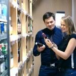 Couple choosing wine in a bottle store — Stock Photo