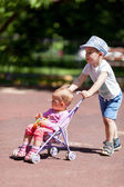 Boy pushing sister in a stroller — Photo