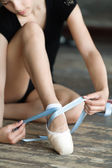 Girl tying her ballet shoes — Stock Photo
