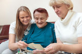 Mother, daughter and grandma looking at photos — Stock Photo