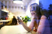 Young woman sitting in a restaurant using a mobile — Стоковое фото