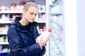 Woman in grocery holding milk — Stock Photo
