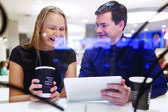 Woman laughs as man shows tablet — Stock Photo