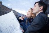 Couple holding blueprints admiring building — Stock Photo