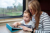 Son and his mom with tablet PC in the train — Foto de Stock