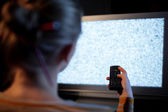 Woman with remote control in front of TV set — Stock Photo