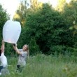 Family flying a fire lantern in the woods — Stock Video #49124109