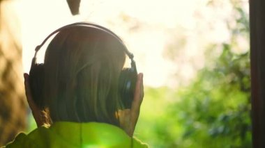Girl listening to music in headphones outdoor — Stock Video