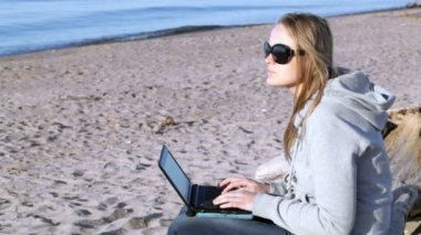 Woman in sunglasses using laptop on the beach — Stock video