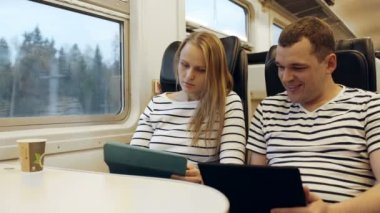 Young people talking in the train looking on the tablet pc — Stock Video