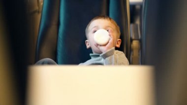 Boy in the train drinking milk from the bottle — Stock Video