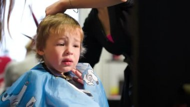 Boy taking off the cape while during haircut — Stock Video