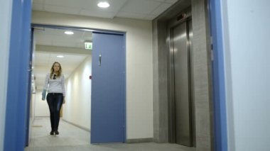 Young woman calling and waiting for elevator — Stockvideo
