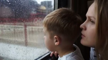 Boy and his mother looking out the window — Stock Video
