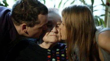 Man and woman kissing grandmother on cheeks — Stock Video