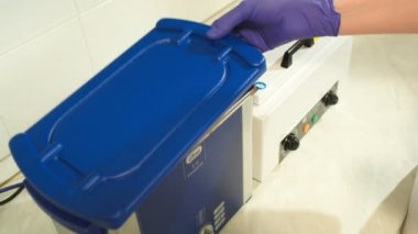 Beautician putting reusable instrument into sterilizer — Stockvideo