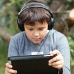 Teen boy in headphones with pad — Stock Photo #49209127
