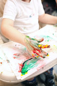 Boy painting with finger-paints — Stock Photo
