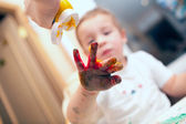 Pressing finger-paint on boys hand — Stock Photo