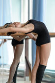 Young ballet dancer stretching out at the barre — Стоковое фото