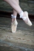 Dancing feet in ballet shoes on wooden floor — Стоковое фото