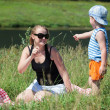 Mother and son playing with grass on the meadow — Stock Photo #50479737