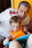 Grandfather and grandson with touch pad — Stock Photo