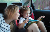 Mother and son with a book in the car — Stock Photo