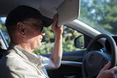 Senior driver hiding from the sun — Stock Photo