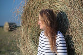 Young woman by the hay roll in the field — Stock Photo